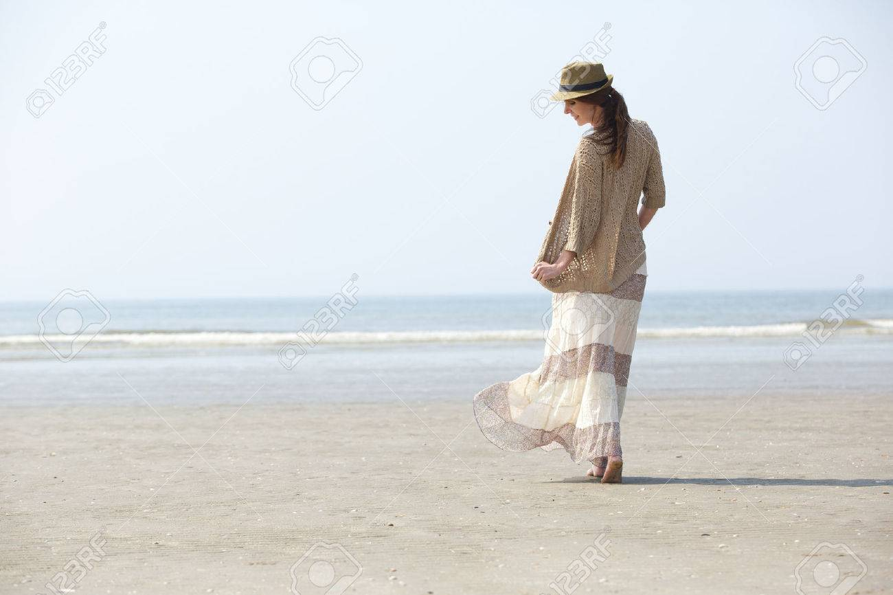 Woman walking on a beach royalty - Rear View Portrait Of A Beautiful Woman Walking On The Beach Stock Photo 27905038