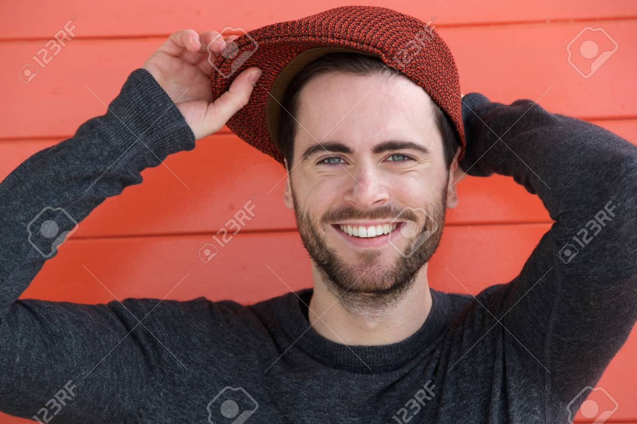 df8a947cf2a Close up portrait of a cute guy with hat posing on orange background Stock  Photo -
