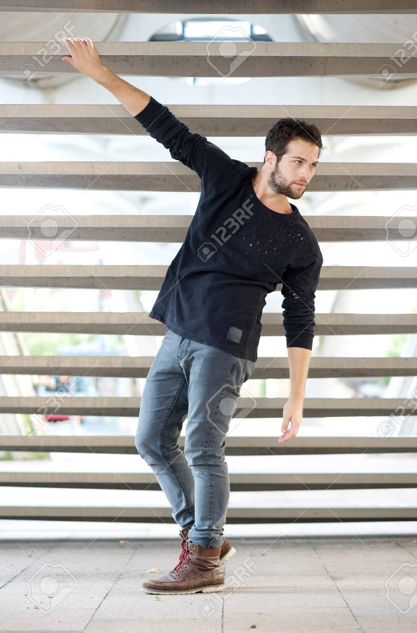Full Length Portrait Of A Male Fashion Model In Black Clothing Posing Outdoors Stock Photo