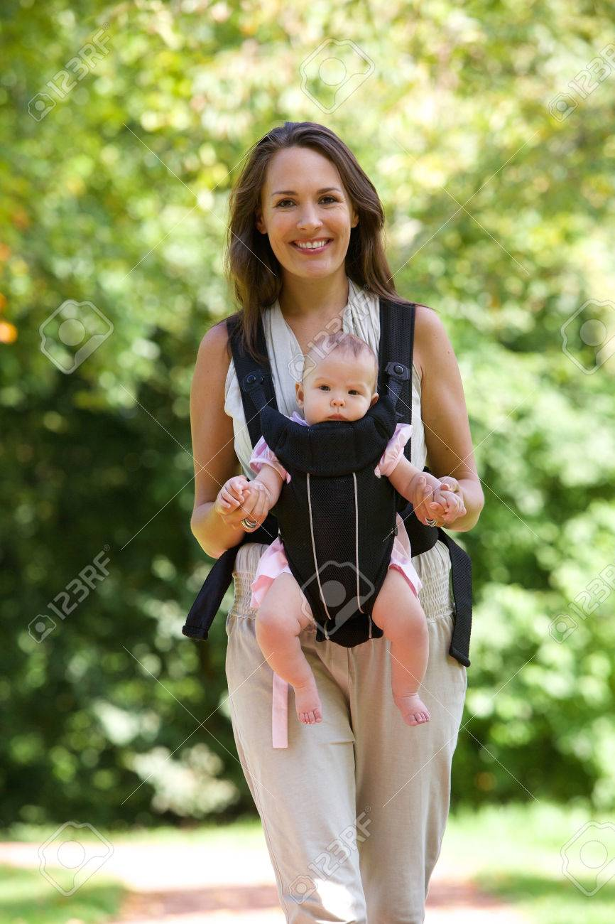 Portrait Of A Happy Mother Walking With Infant In Baby Carrier