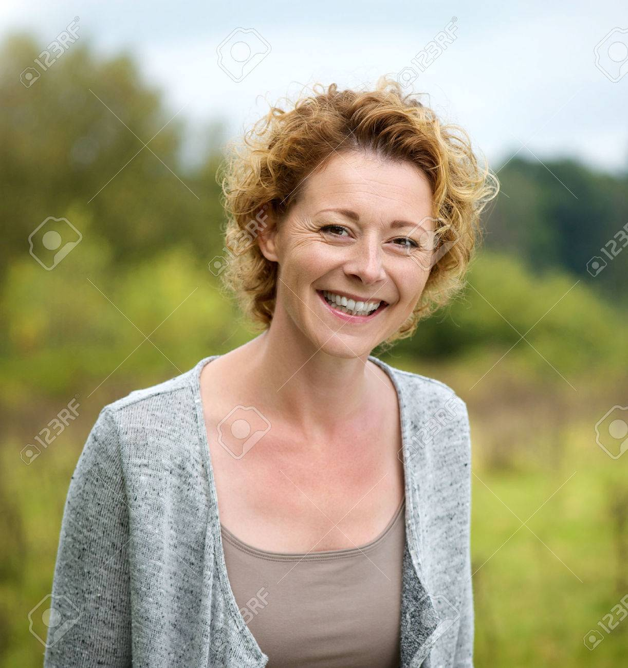close up portrait of a beautiful mature woman smiling in the.. stock