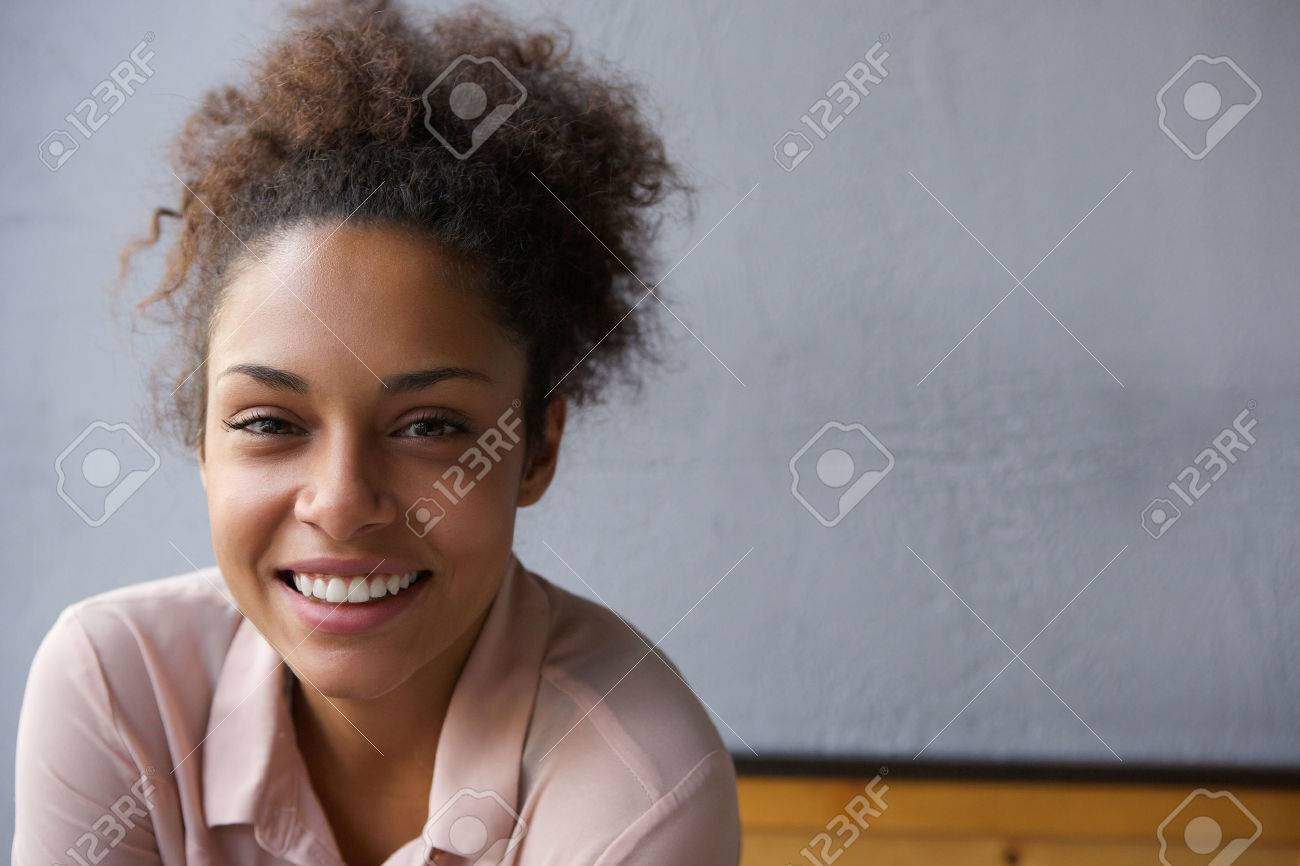 Close up portrait of a happy young black woman smiling - 33727922