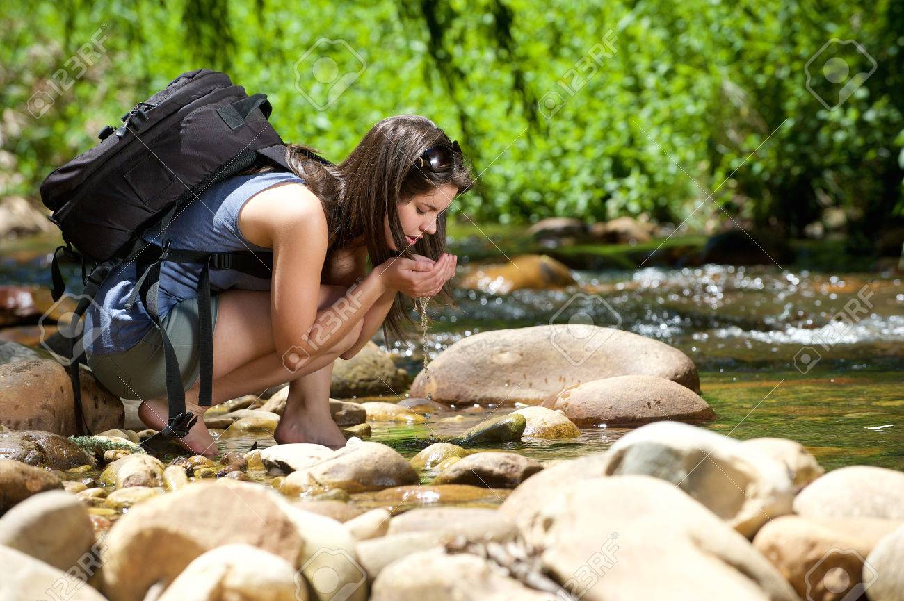 Young woman drinking water from outdoor stream with her hands - 37097775