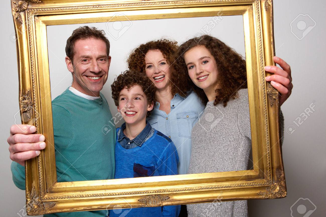 Portrait Of A Happy Family Holding Picture Frame And Smiling Stock ...