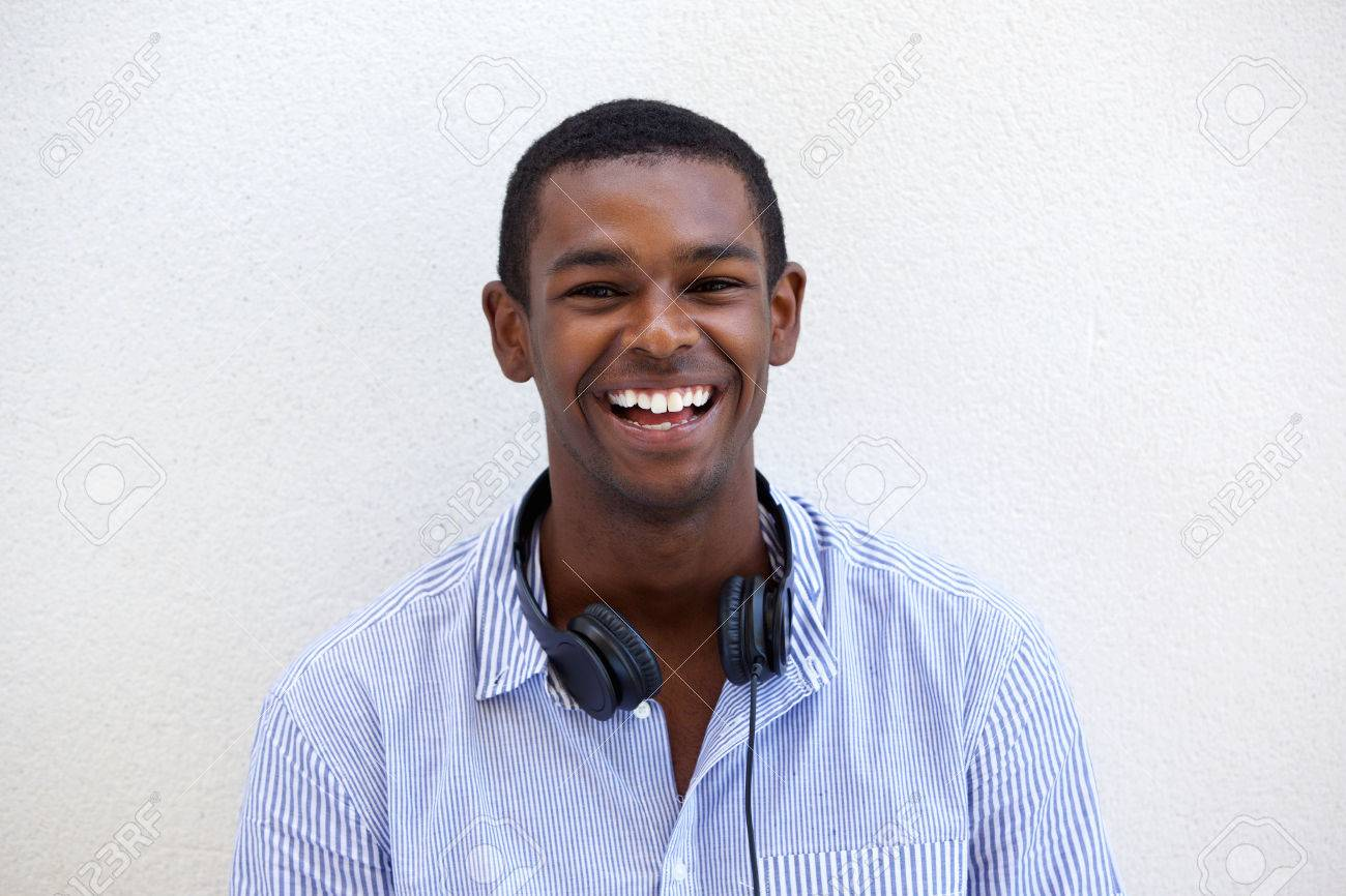 cbc30535f75 Close up portrait of a happy young black man smiling with headphones on  white background Stock