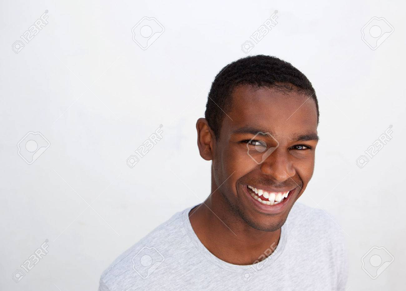 close up portrait of a laughing black guy posing against white