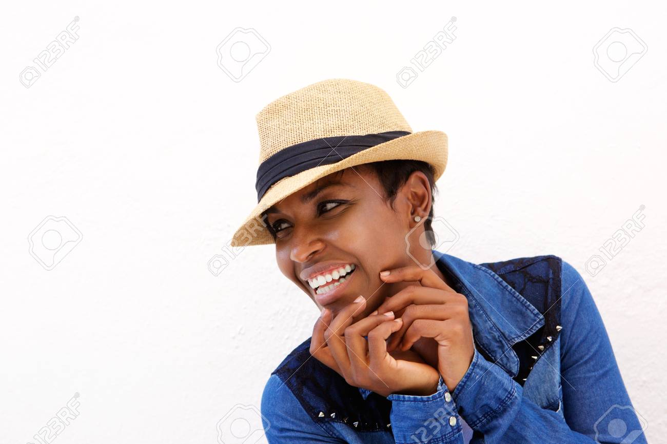 dc153eea40e Close up portrait of a young black woman smiling against white background  with hat Stock Photo