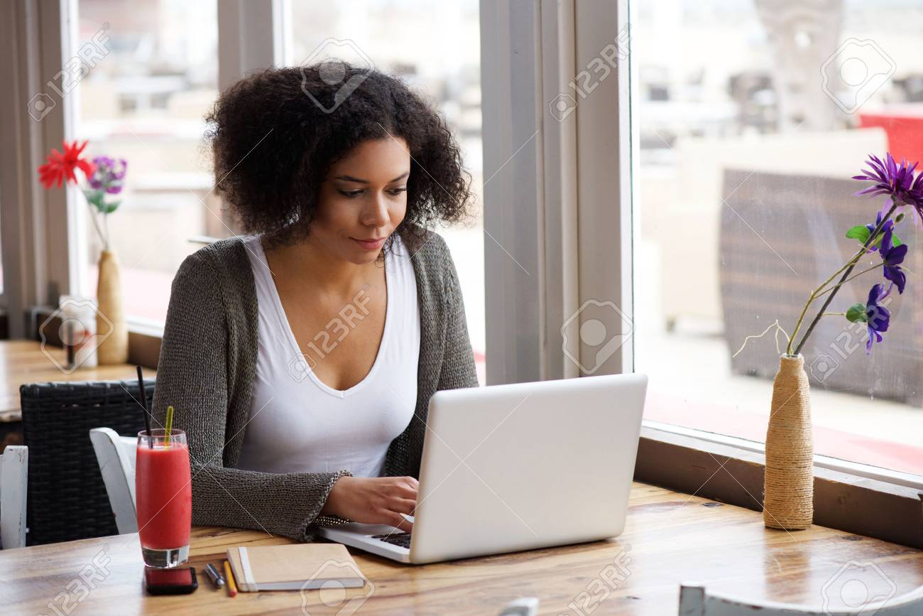 Portrait of an african american young woman sitting at cafe with laptop writing her blog - 45866817
