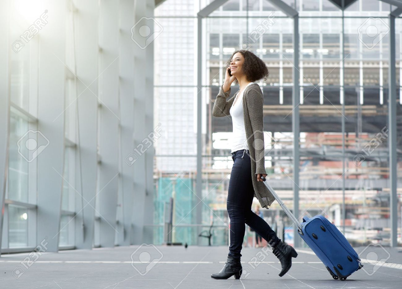 Full length side portrait of a traveling young woman with mobile phone and suitcase Stock Photo - 45866907