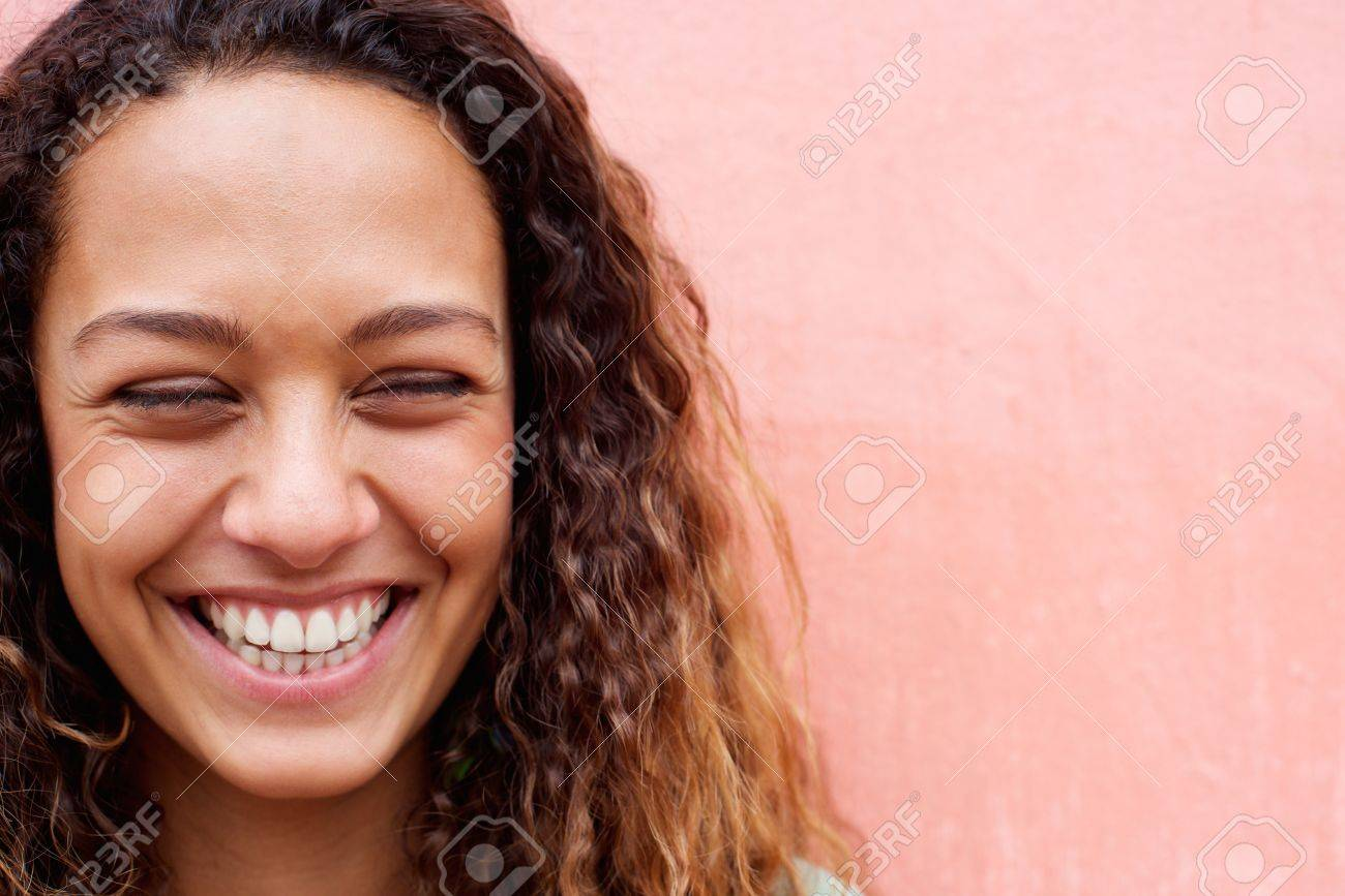 Close up portrait of laughing young woman with curly hair - 50593566