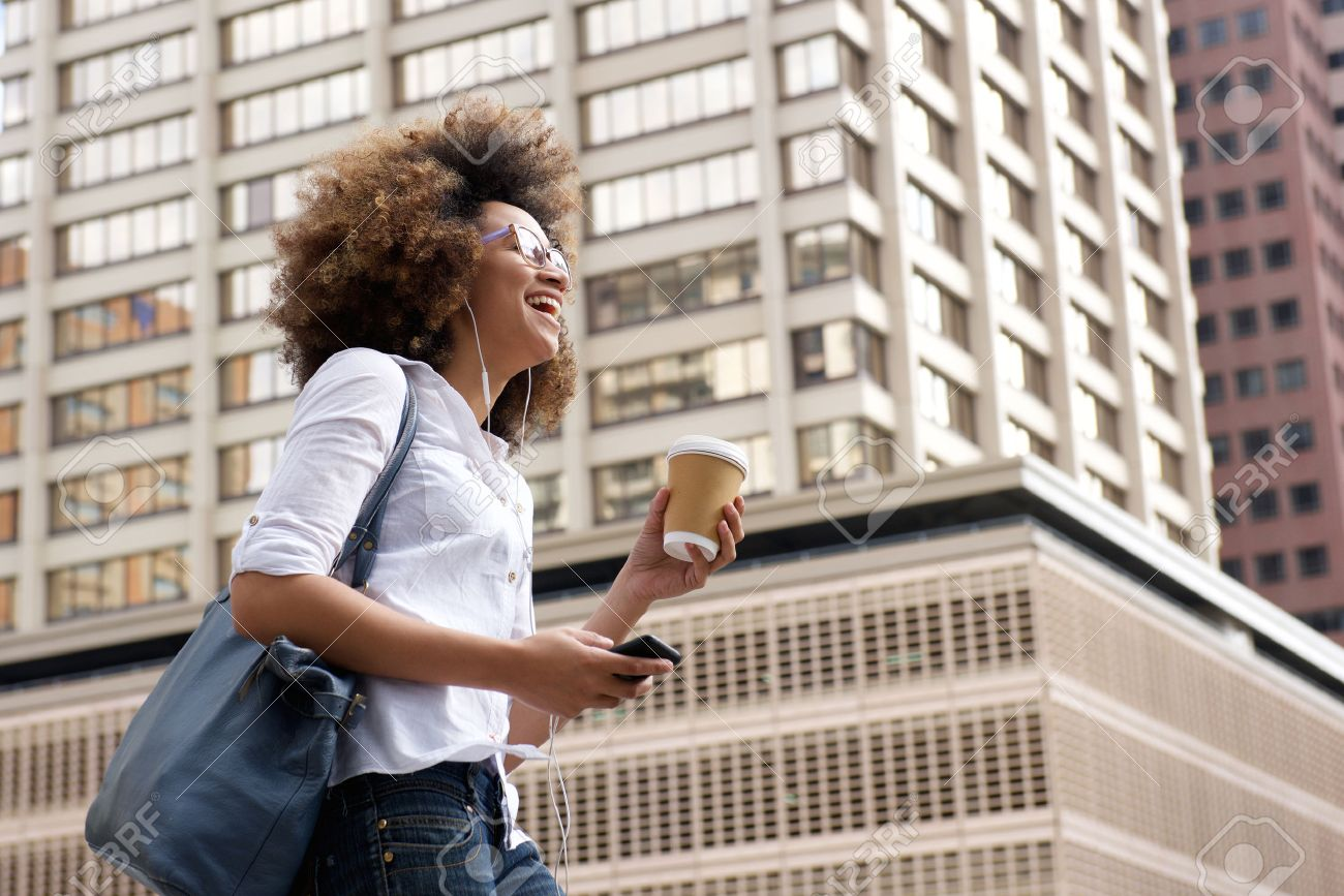 Side portrait of a smiling african american woman walking in the city with cellphone Standard-Bild - 50874104