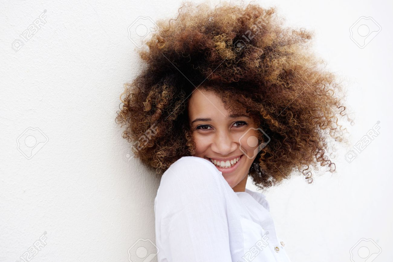 Close up portrait of a young woman smiling with afro hair against white background Standard-Bild - 50874046