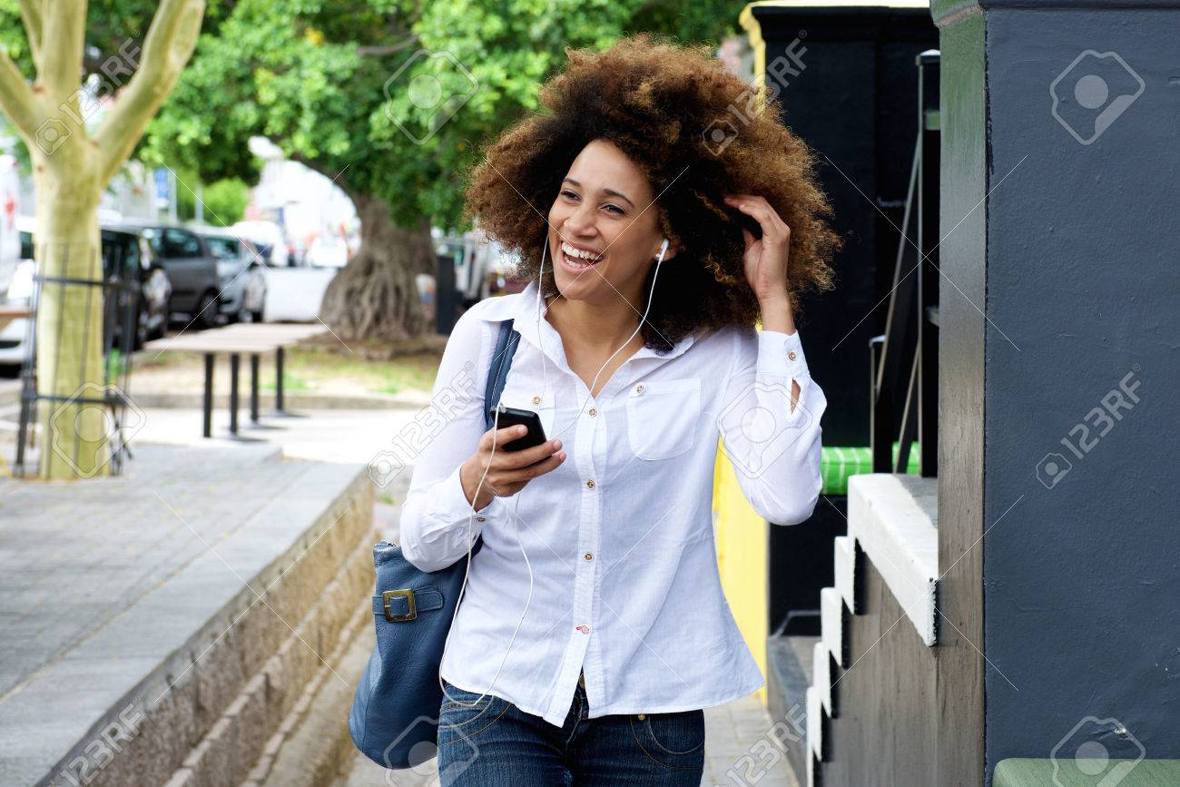 Portrait of young woman smiling with earphones and smart phone - 50873679
