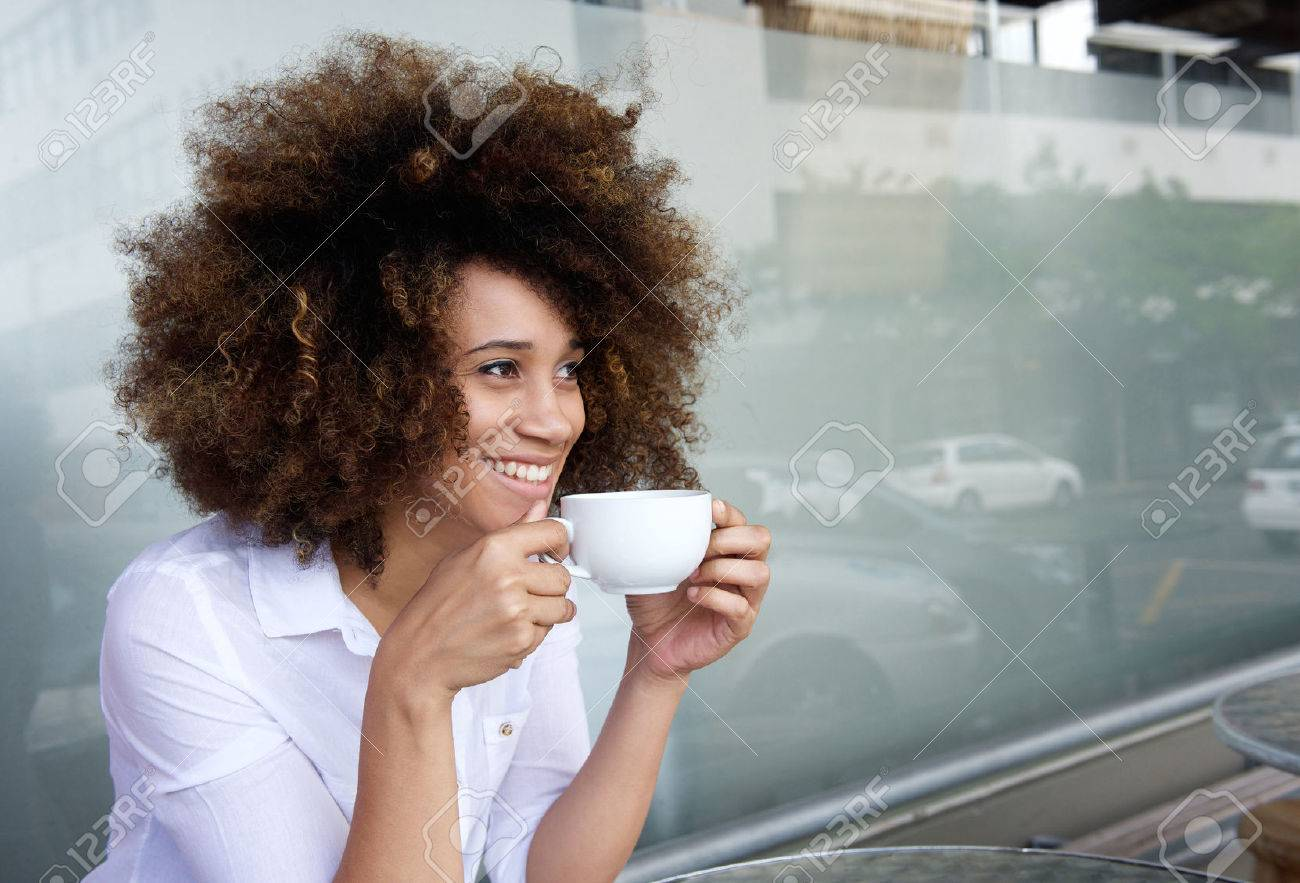 Portrait of smiling african american woman sitting with cup of coffee Standard-Bild - 50873592