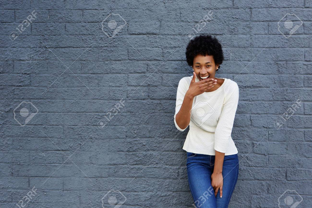 Portrait of happy african woman covering her mouth and laughing against a gray wall - 51497359