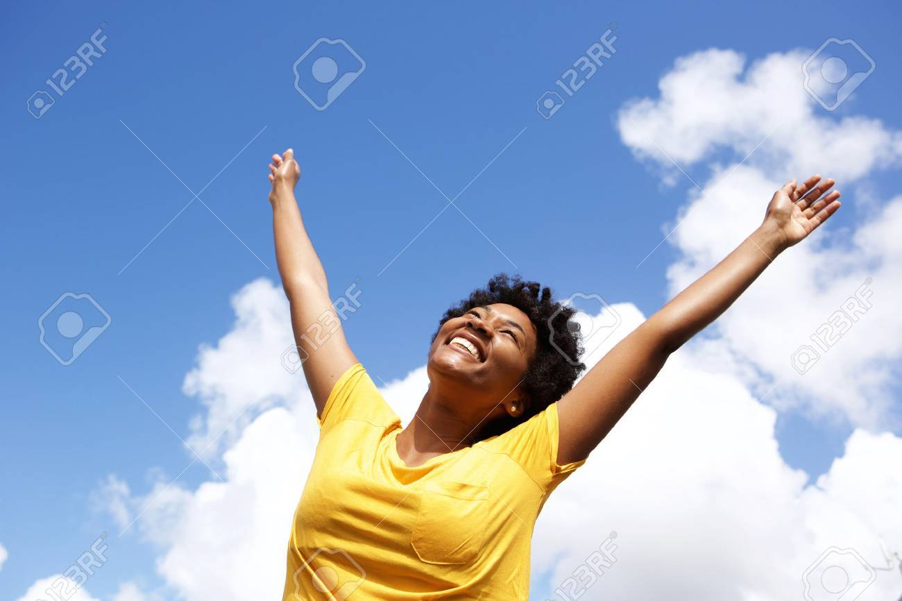 Portrait of cheerful young woman standing outside with her hands raised towards sky - 51497462