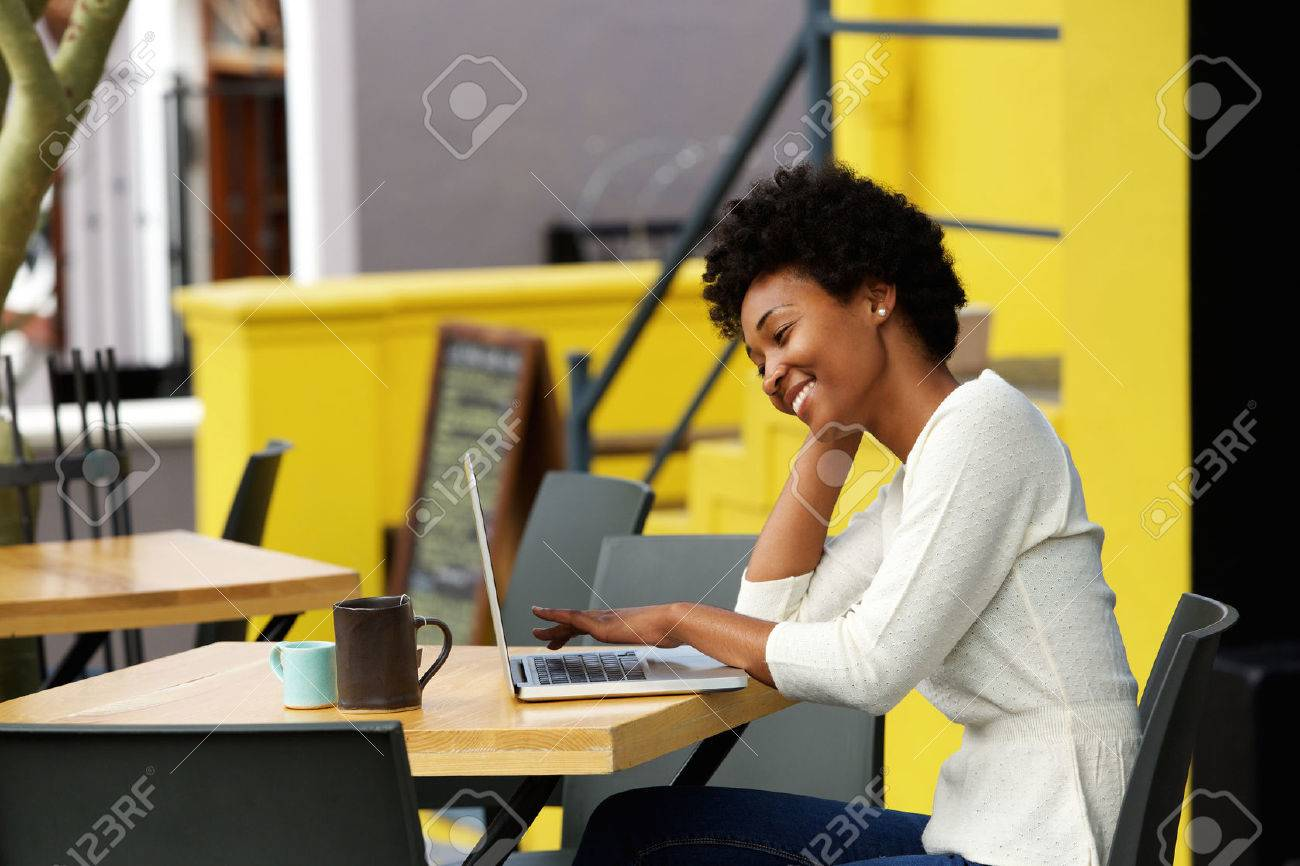 Portrait of a happy young african woman relaxing in outdoor cafe and using a laptop Standard-Bild - 51497479
