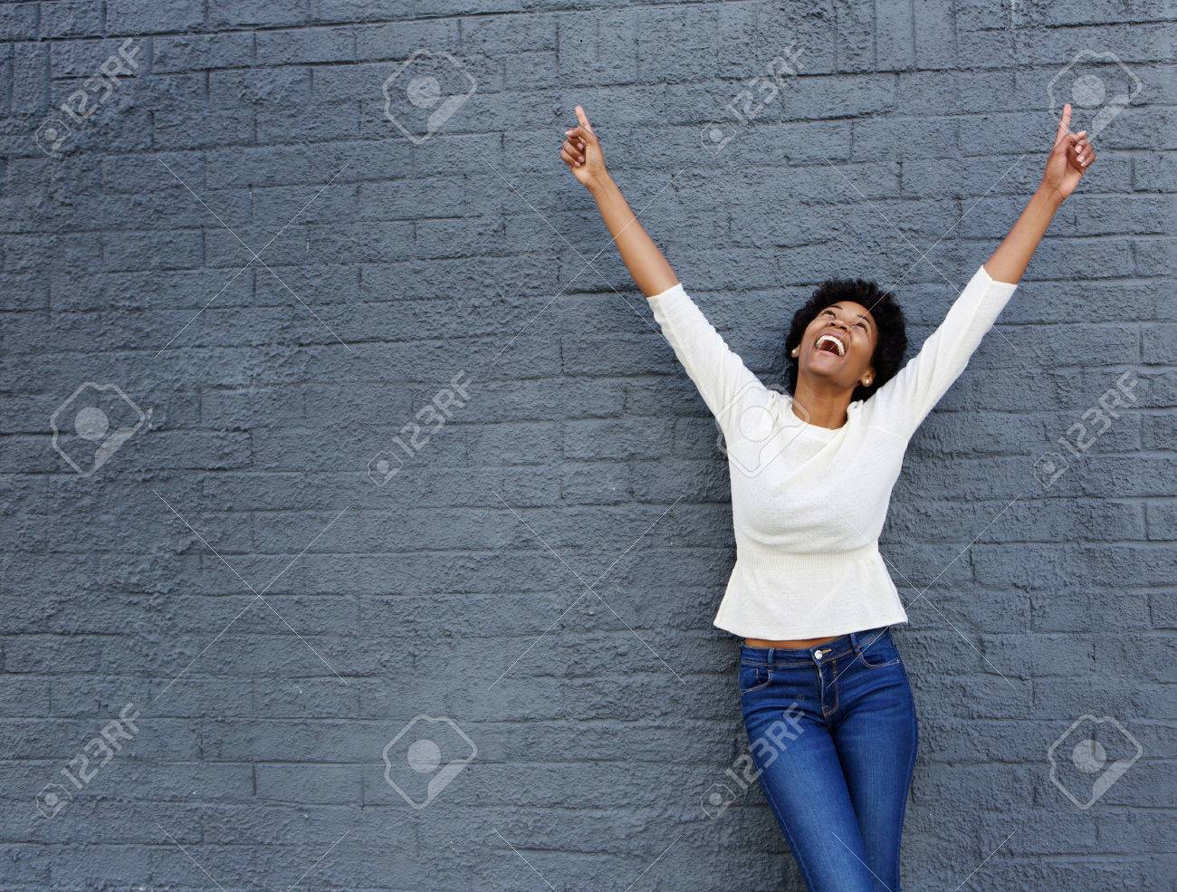Portrait of a cheerful african woman with hands raised pointing up Standard-Bild - 51497506