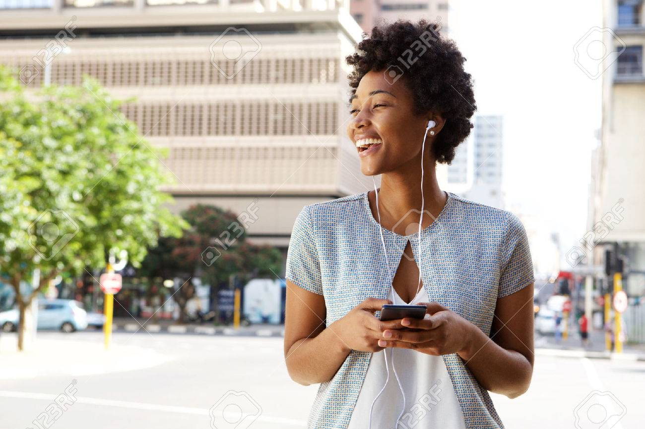 Portrait of cheerful young lady out on the city street listening to music on her mobile phone Standard-Bild - 51497531