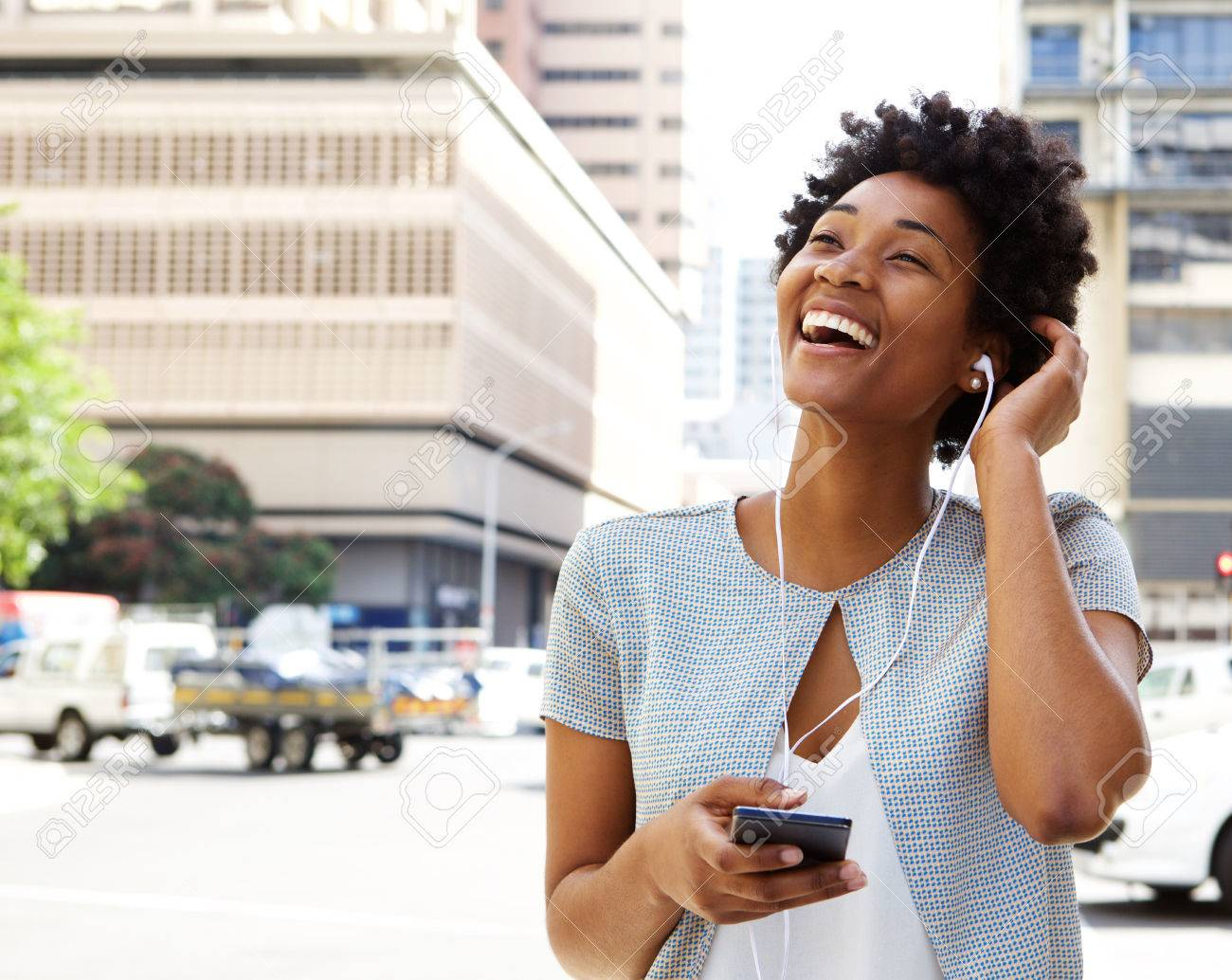 Portrait of smiling young african american woman listening to music on headphones outdoors on city street Standard-Bild - 51497785