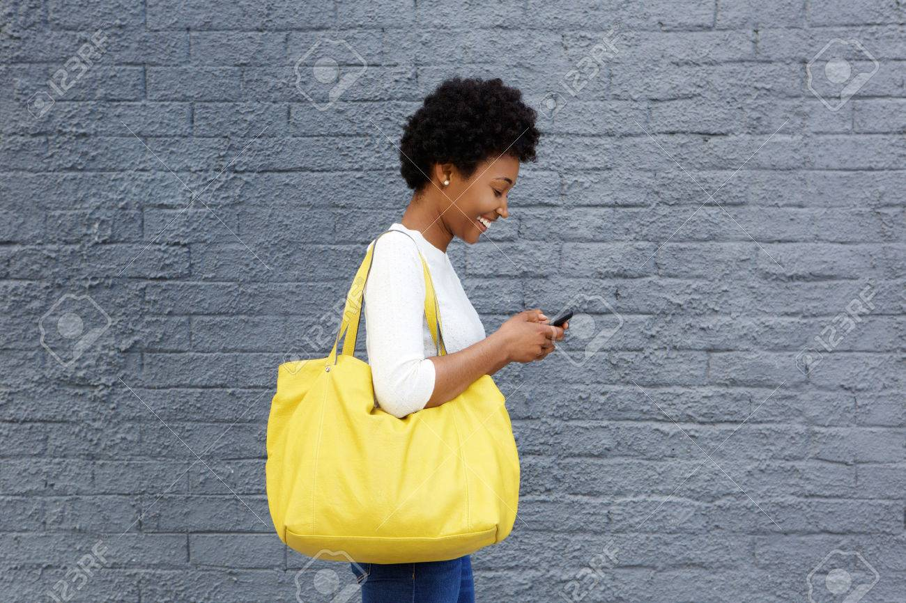 Side portrait of a happy young woman with a bag reading text message on her mobile phone Standard-Bild - 51497841