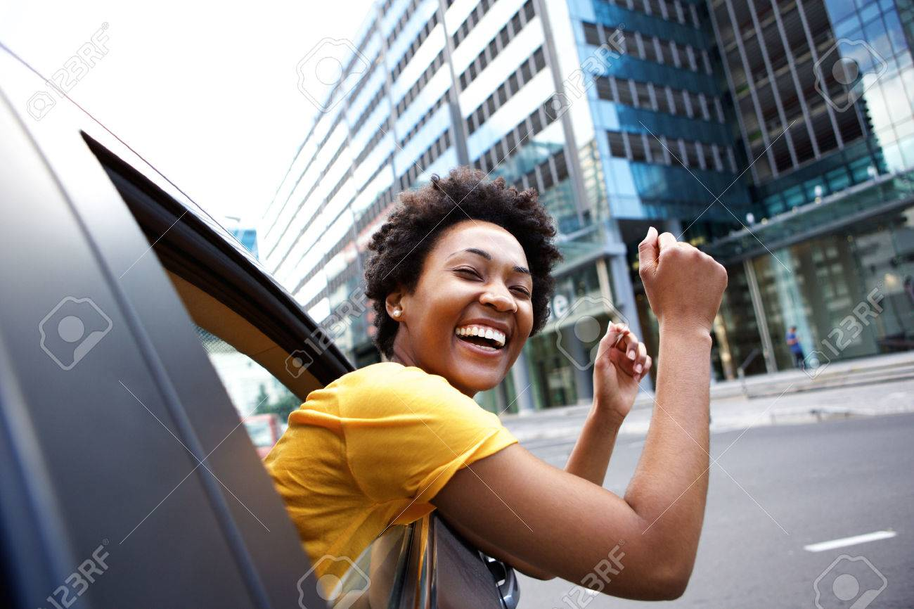 Portrait of cheerful young african woman looking out the car window with her arms raised Standard-Bild - 51497845