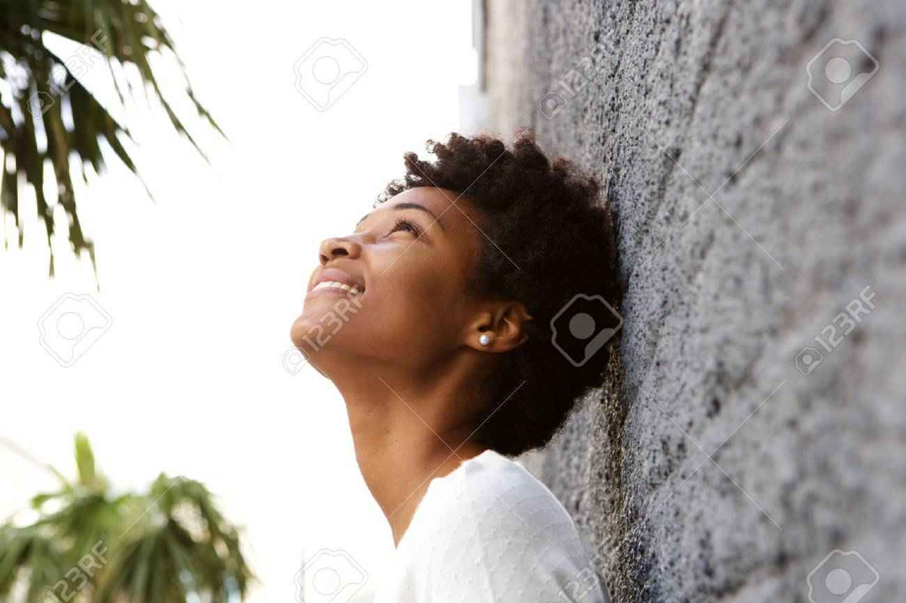 Side portrait of young african woman leaning to a wall outside and looking up Standard-Bild - 51497823