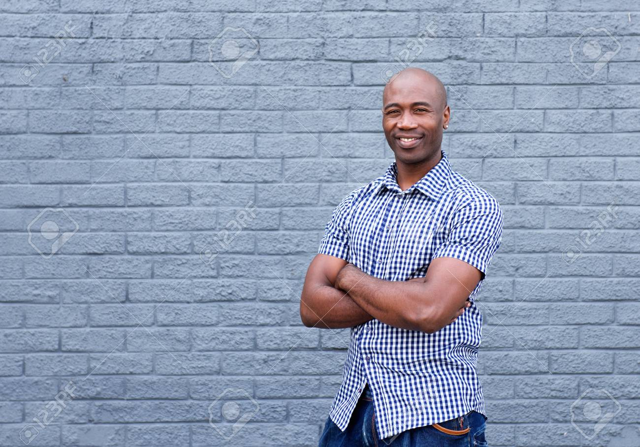 Portrait of smiling african american man standing with arms crossed against a gray wall - 51497857