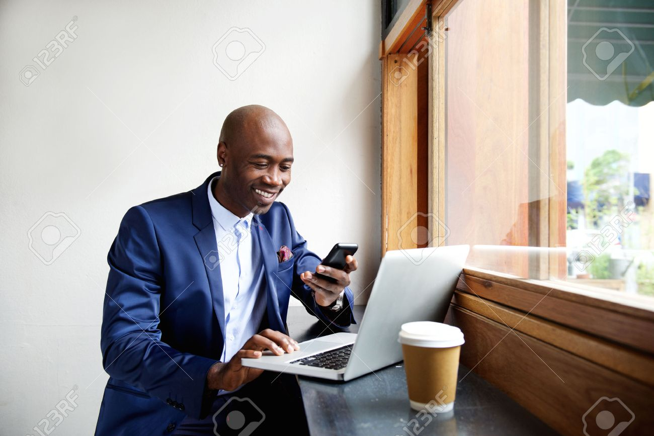 Portrait of happy african businessman using phone while working on laptop in a restaurant Standard-Bild - 51498038
