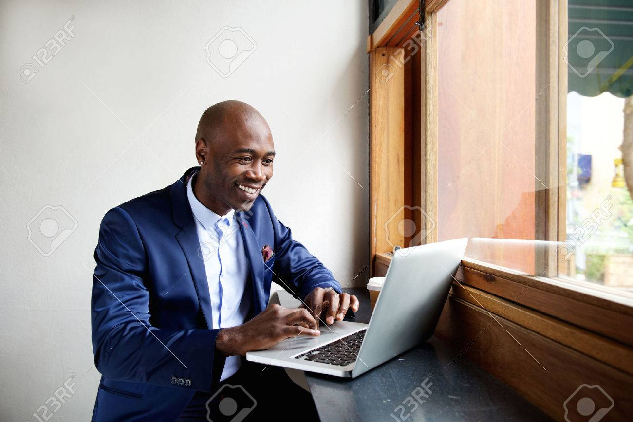 Portrait of happy african businessman sitting in a cafe and working on laptop Standard-Bild - 51498327