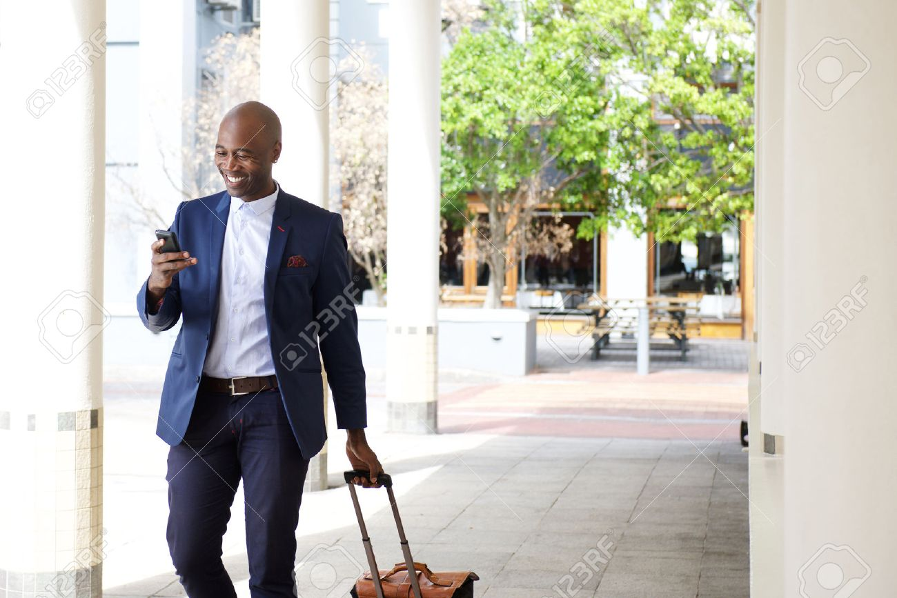 Portrait of businessman traveling with a bag and mobile phone Standard-Bild - 51498361