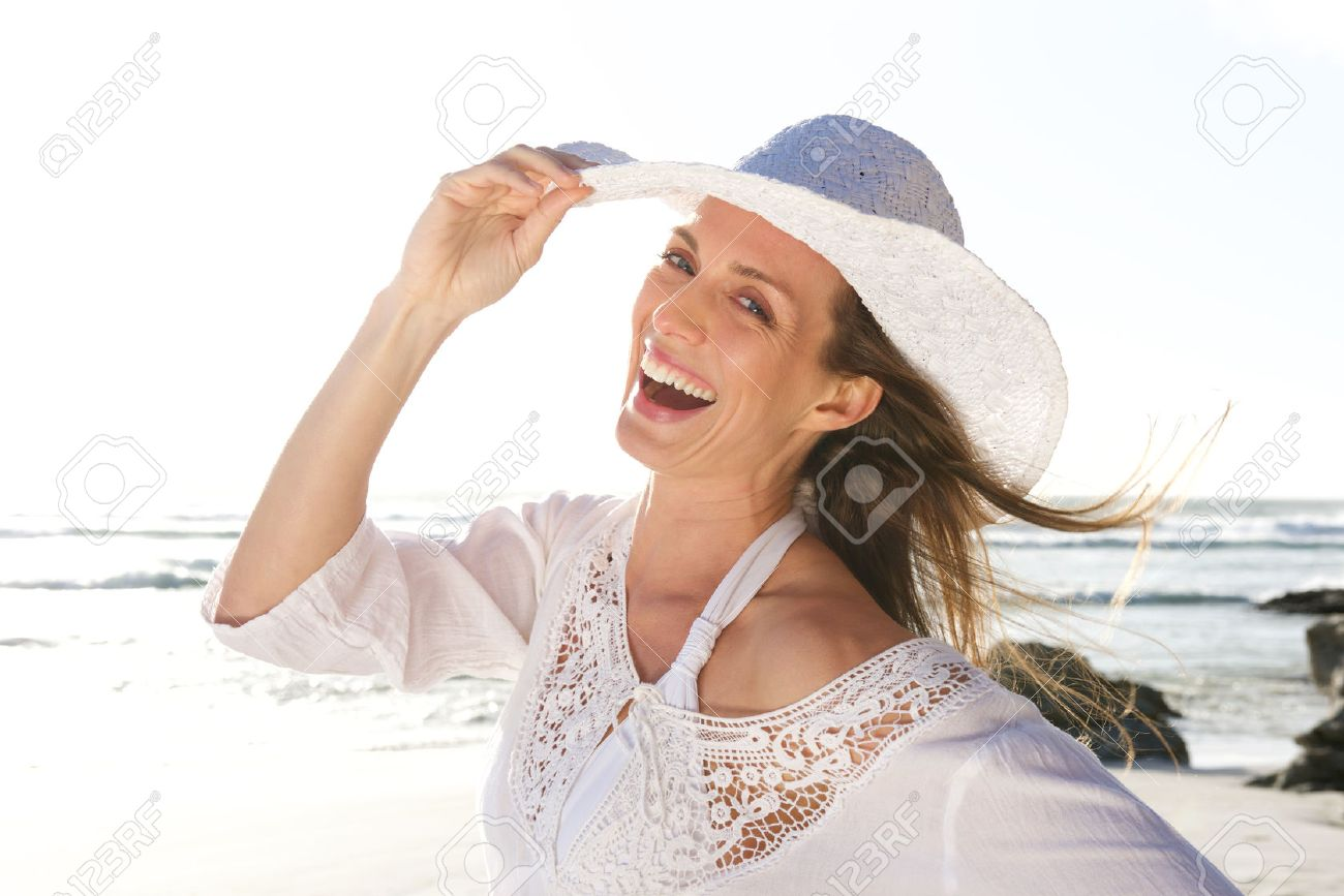 Close up portrait of an attractive woman laughing with hat at the beach Standard-Bild - 51907315