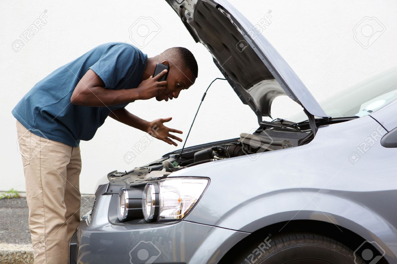 Side portrait of a young african man having trouble with his broken car calling for help on cell phone. Standard-Bild - 52531538