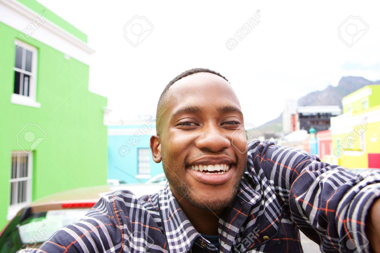 Close up of happy young man on the city street taking a self portrait Standard-Bild - 52531725
