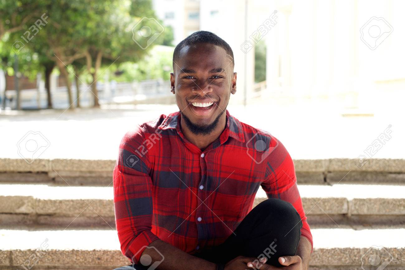 Close up portrait of smiling young african man sitting outdoors on steps Standard-Bild - 53348751