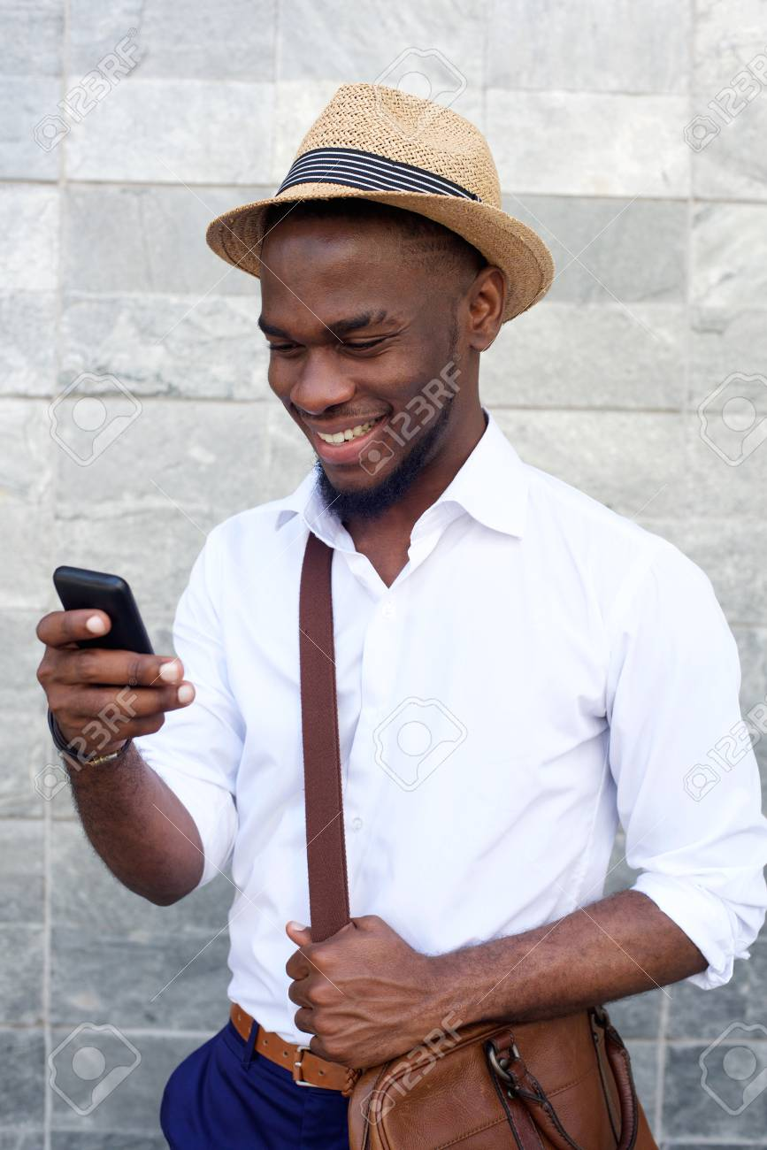 Close up portrait of a cool young african guy with hat and bag looking at  mobile 289932163e7