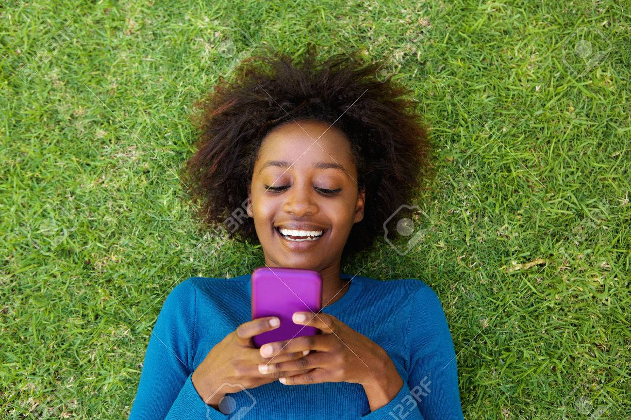 Portrait from above of a smiling african woman lying on grass looking at cell phone Standard-Bild - 53357923