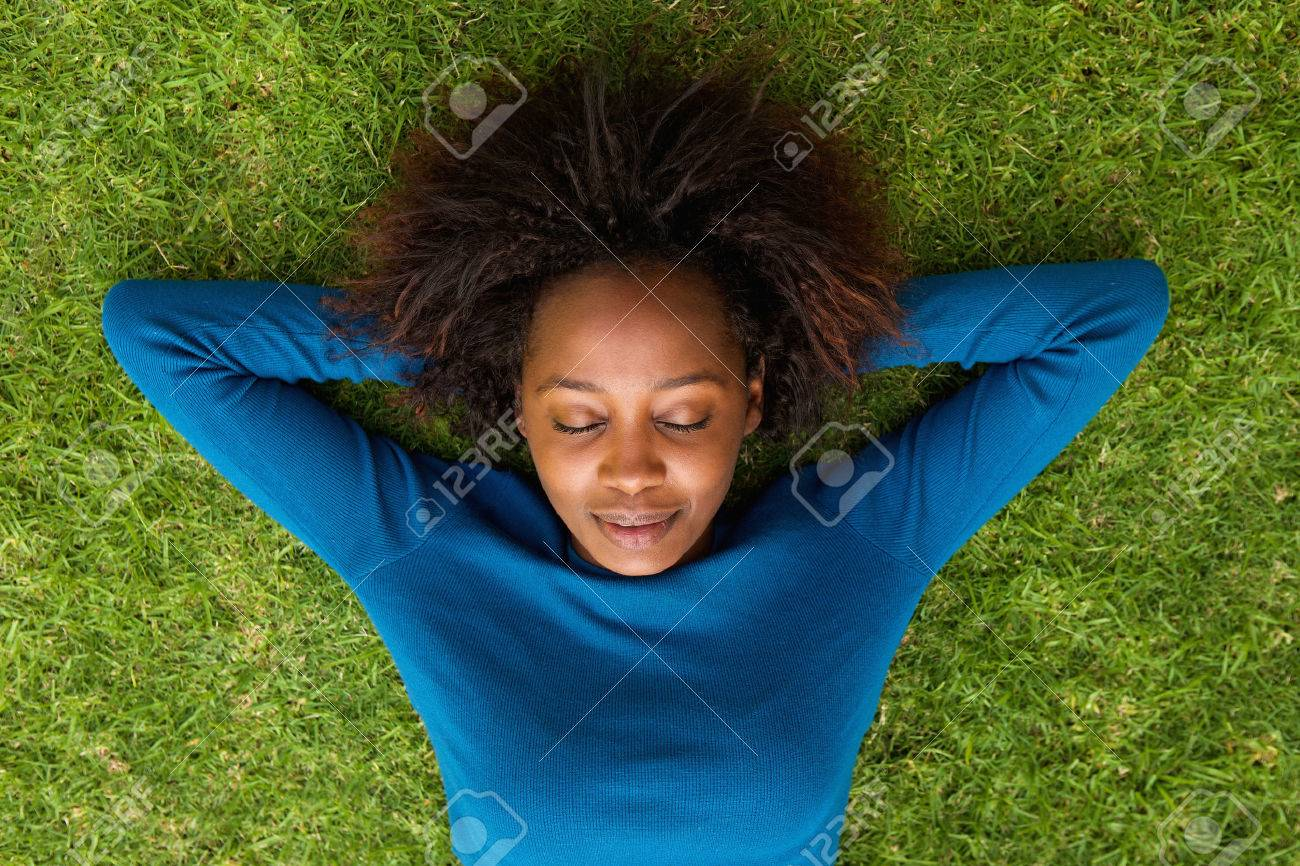 Portrait from above of a young african woman lying on grass sleeping - 53360178