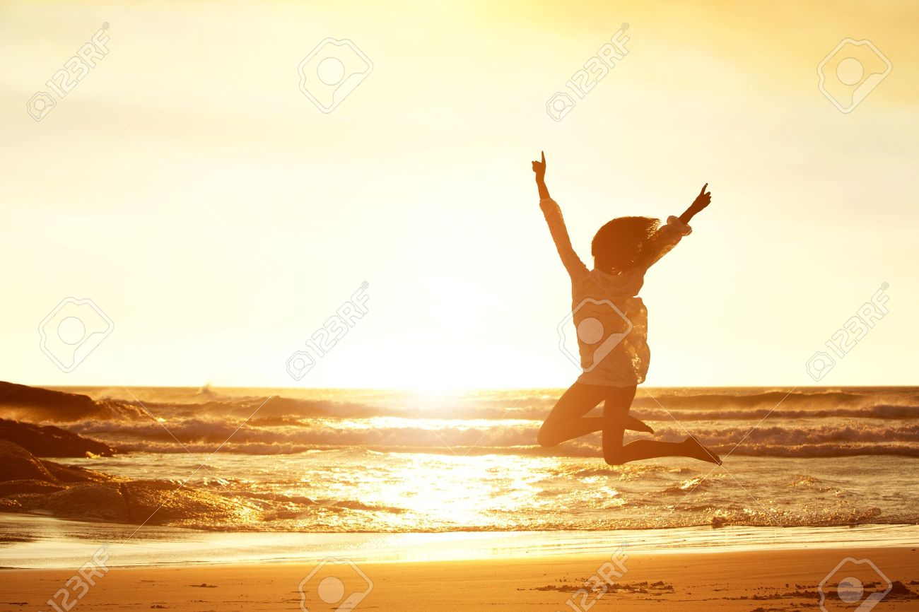 Silhouette portrait of young woman jumping for joy at beach during sunset Standard-Bild - 53754094