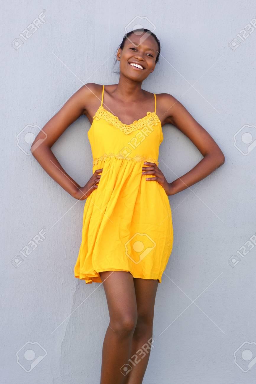 43fd66734f36 Banque d images - Portrait d un beau modèle de mode noir posant en robe  jaune contre le mur gris