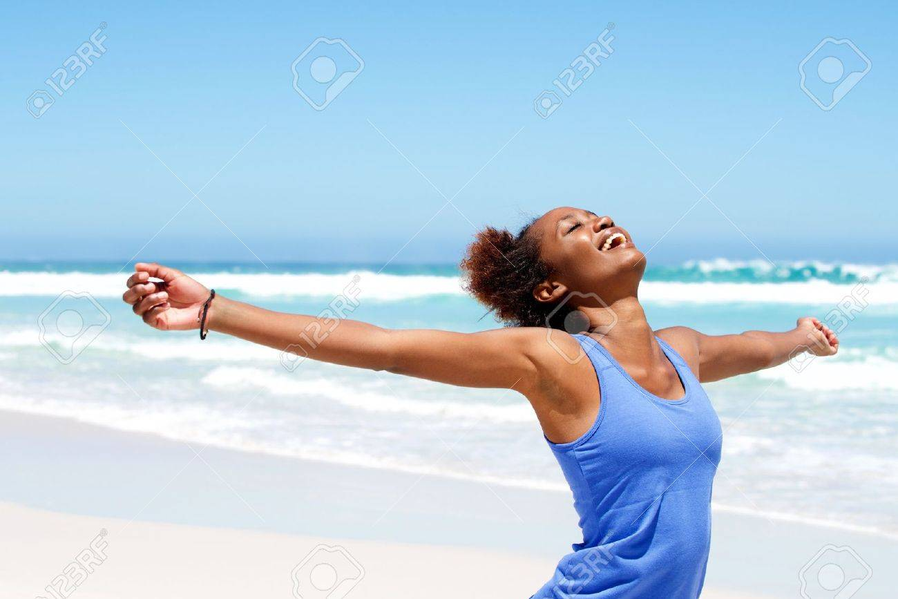 Portrait of healthy young african woman standing on the beach with her hands outstretched Standard-Bild - 54908552