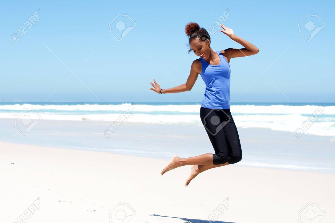 Portrait of young sporty woman jumping with joy at the beach Stock Photo - 54908560