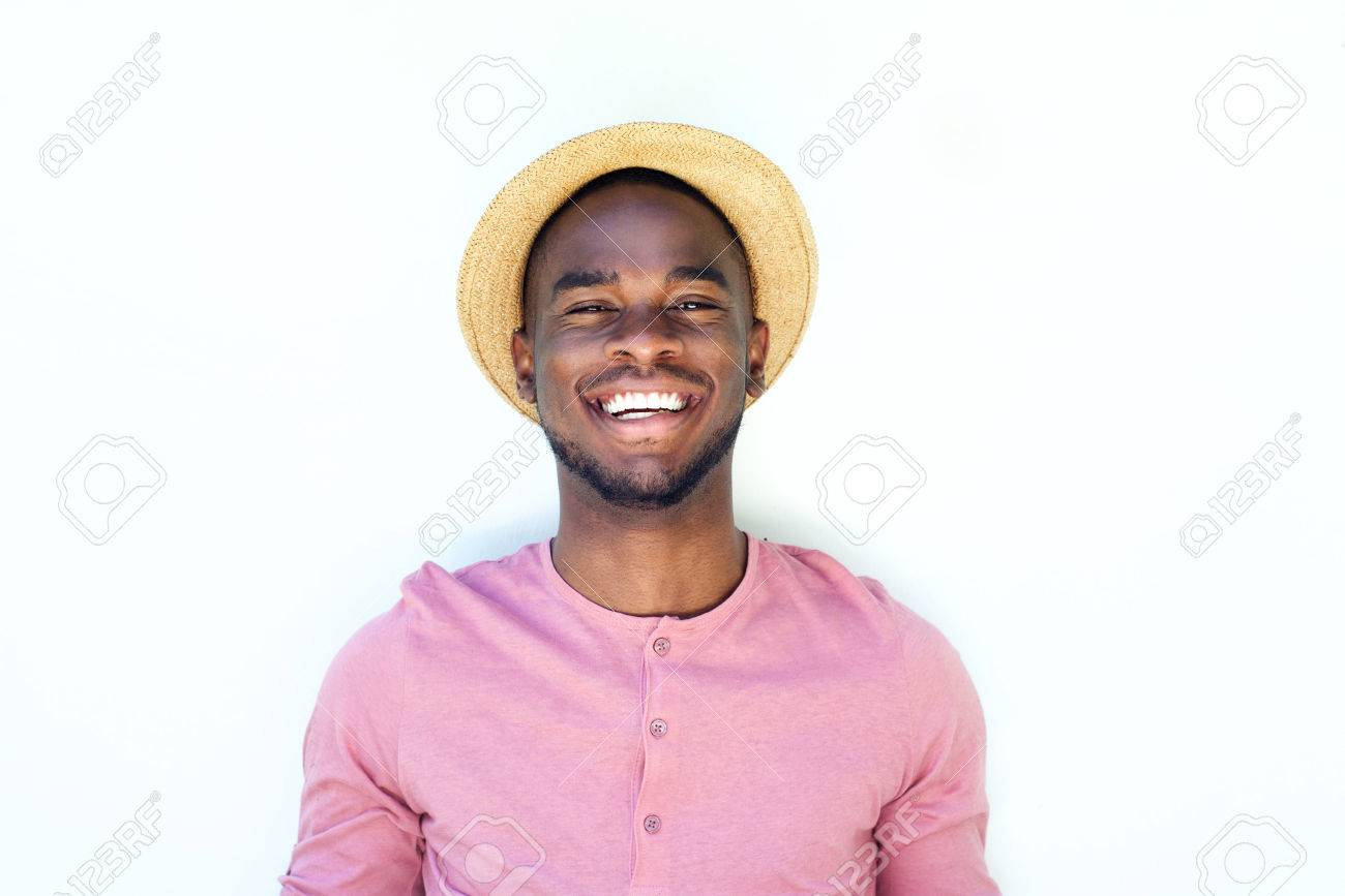 0d4807c2521 Close up portrait of a smiling young black guy with hat against white  background Stock Photo
