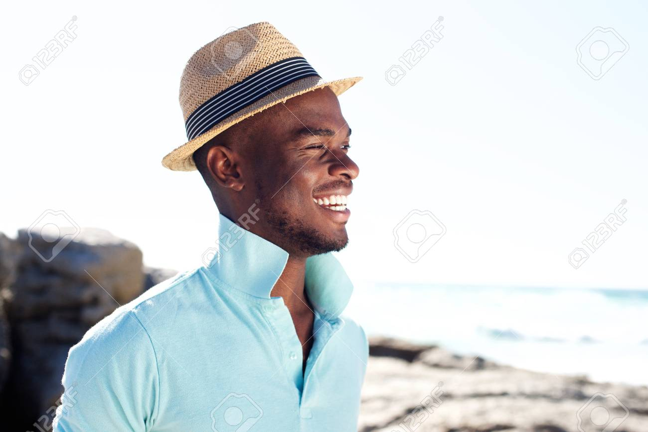 Side portrait of handsome young guy with hat smiling at the beach Stock  Photo - 56108909 b34ac2a592f