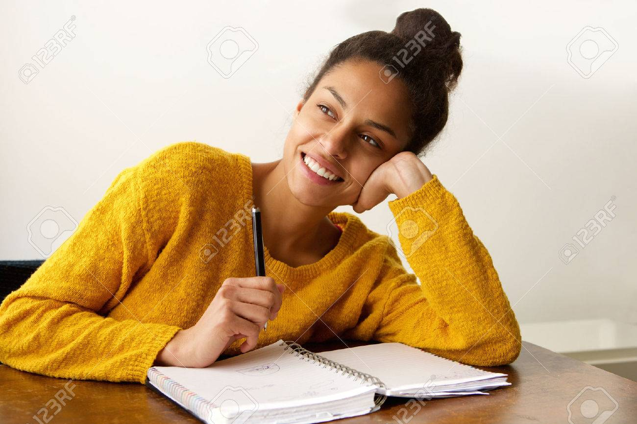 Portrait of a smiling female student thinking with with pen and paper Standard-Bild - 59412758