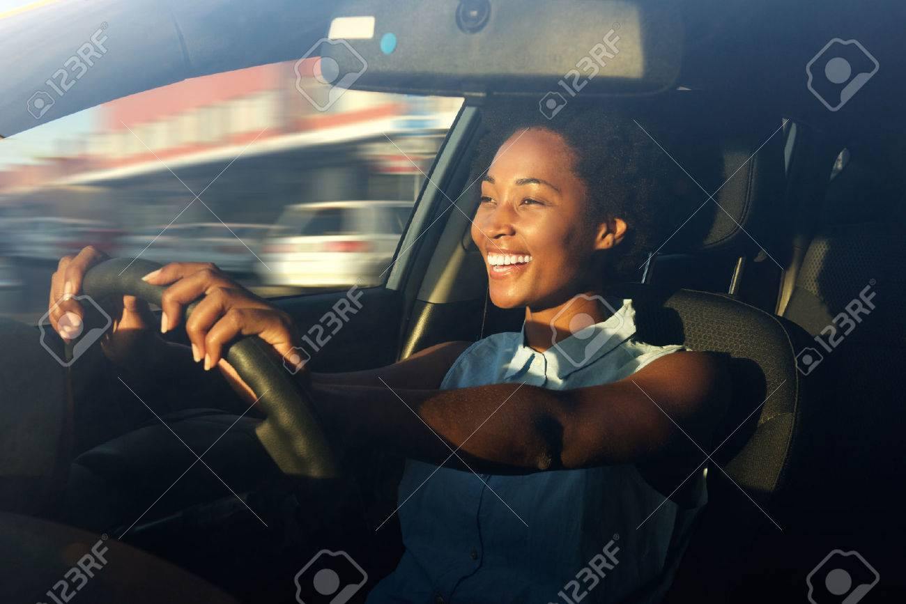 Portrait of smiling young african american woman driving a car - 60626289
