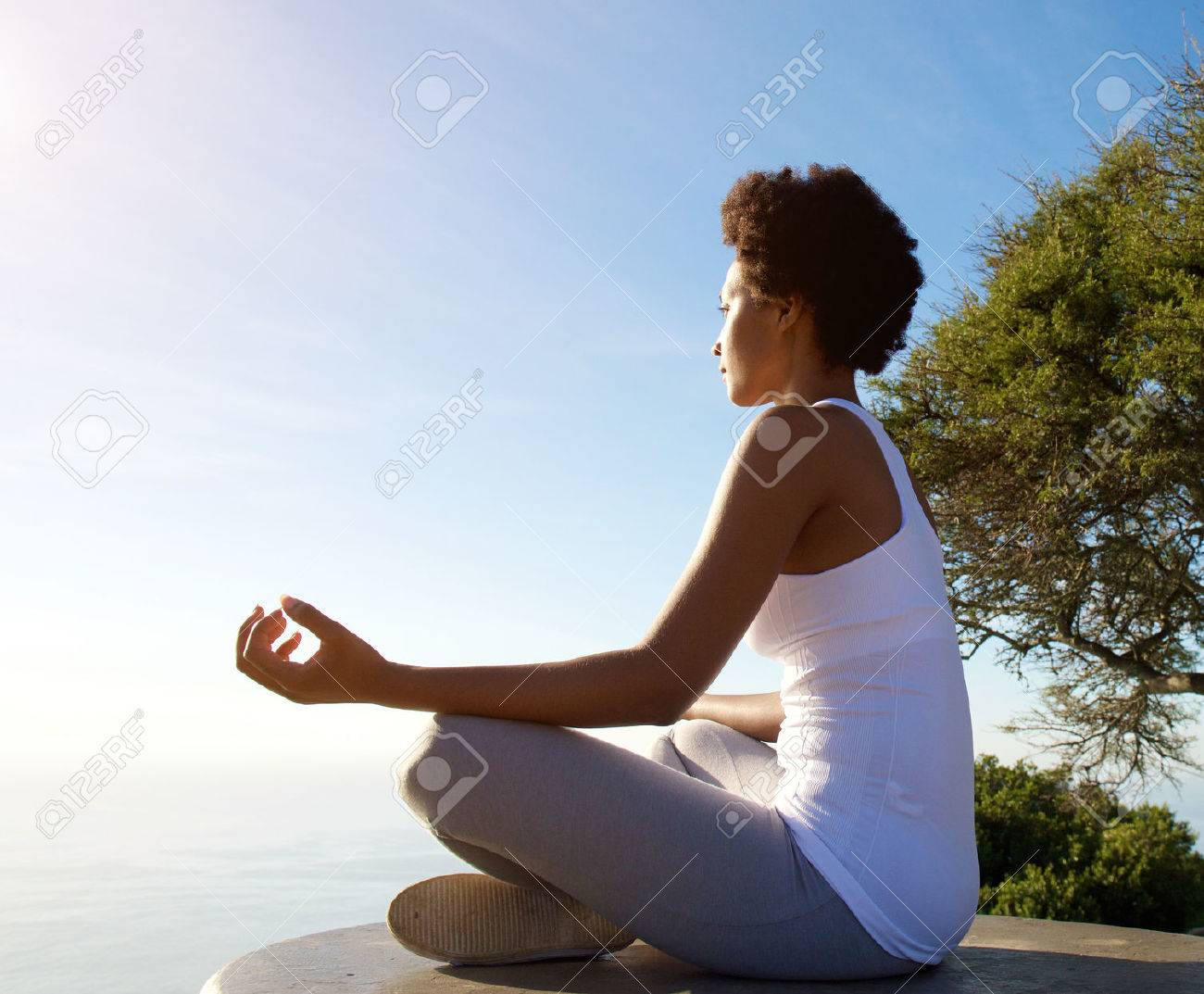 Side portrait of beautiful young woman sitting in yoga pose at beach Standard-Bild - 60626324