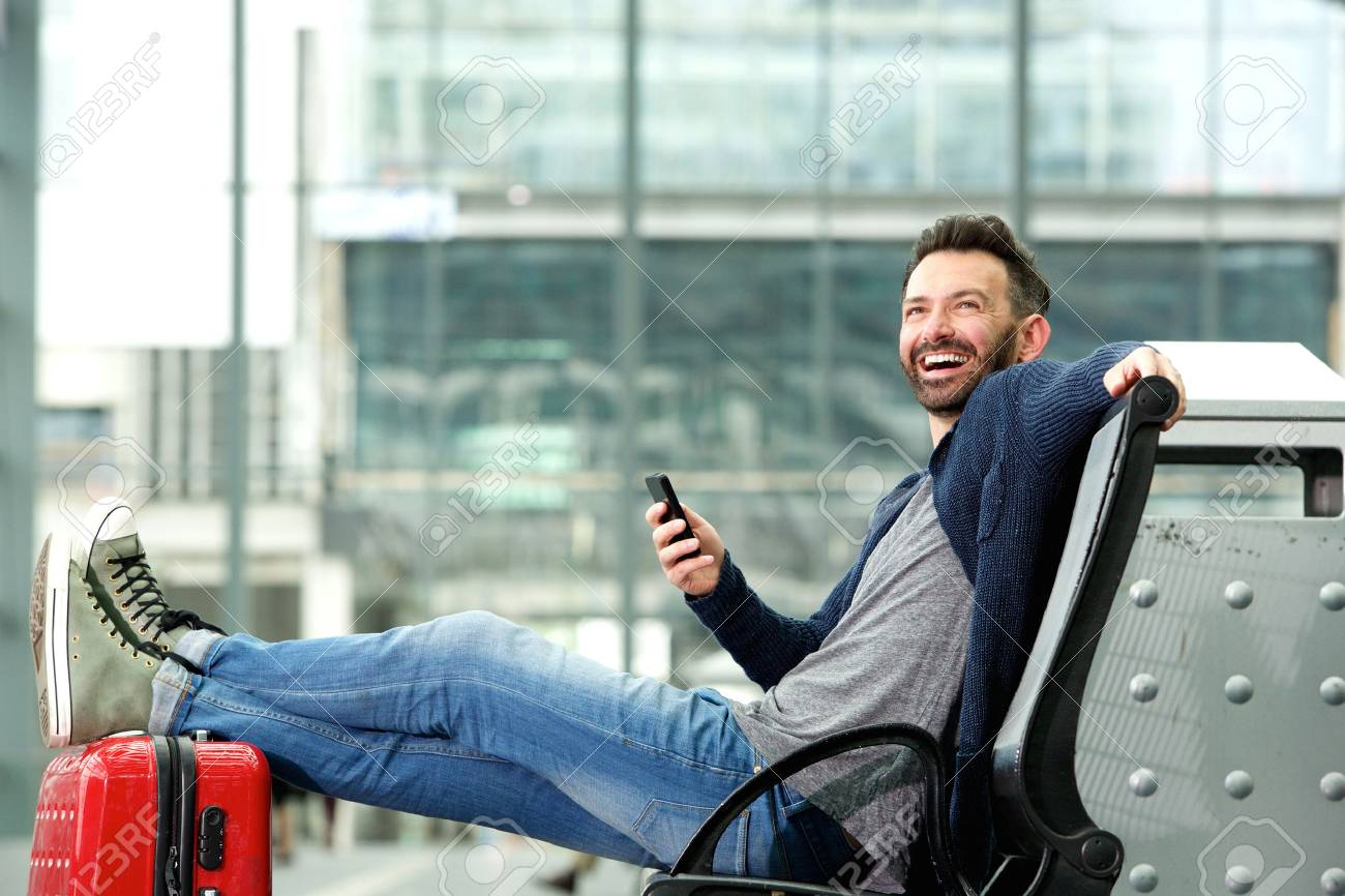 Portrait of happy mature man sitting with travel bag and mobile phone at the train station - 62984737