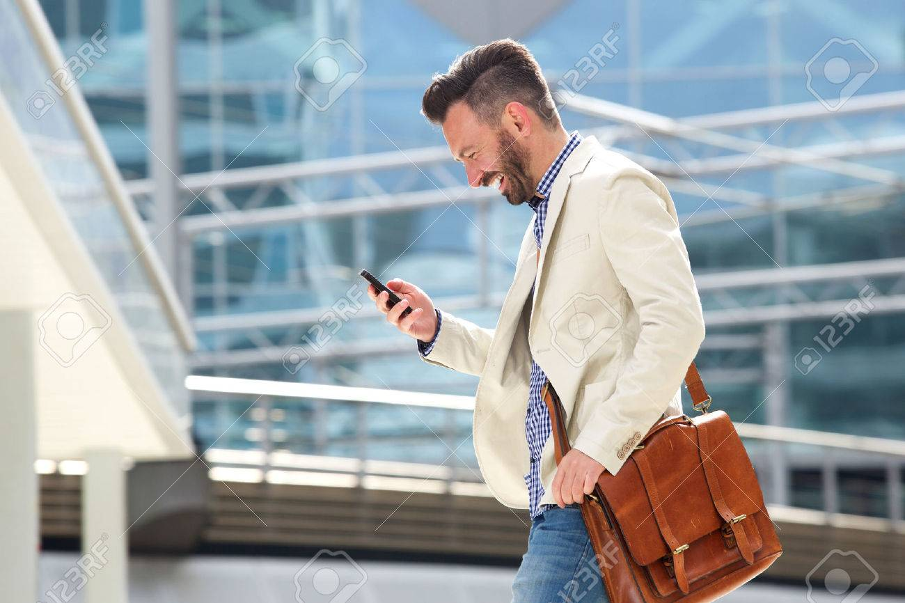 Side portrait of smiling mature man with bag walking outdoors and reading text message on his cell phone Standard-Bild - 62984894