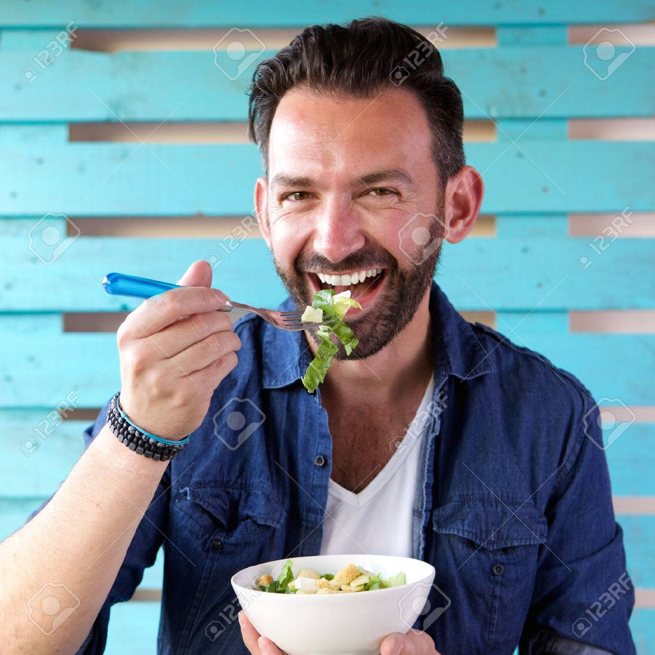 Close up portrait of cheerful man eating salad from bowl - 63536620